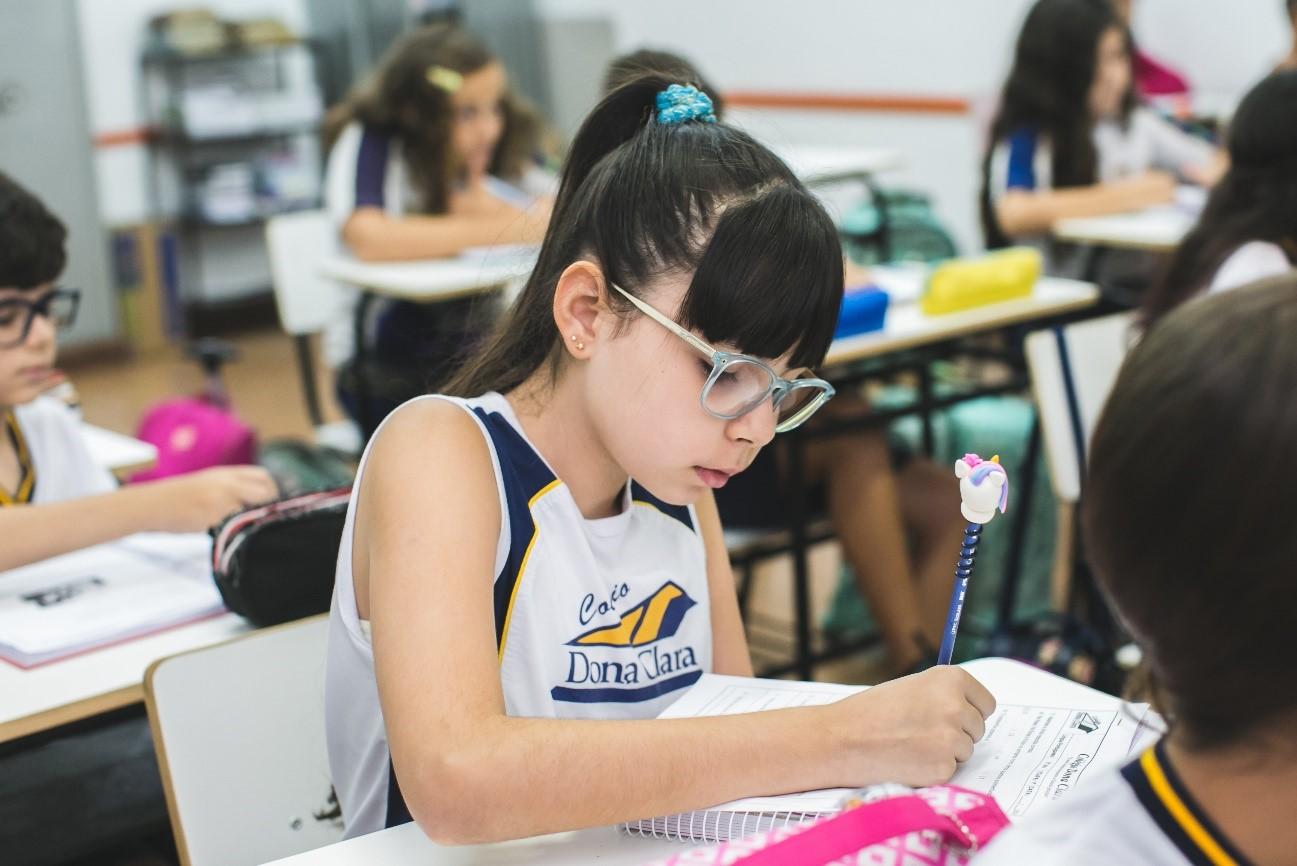 Aluna sentada em carteira em sala de aula ampliando seu vocabulário infantil