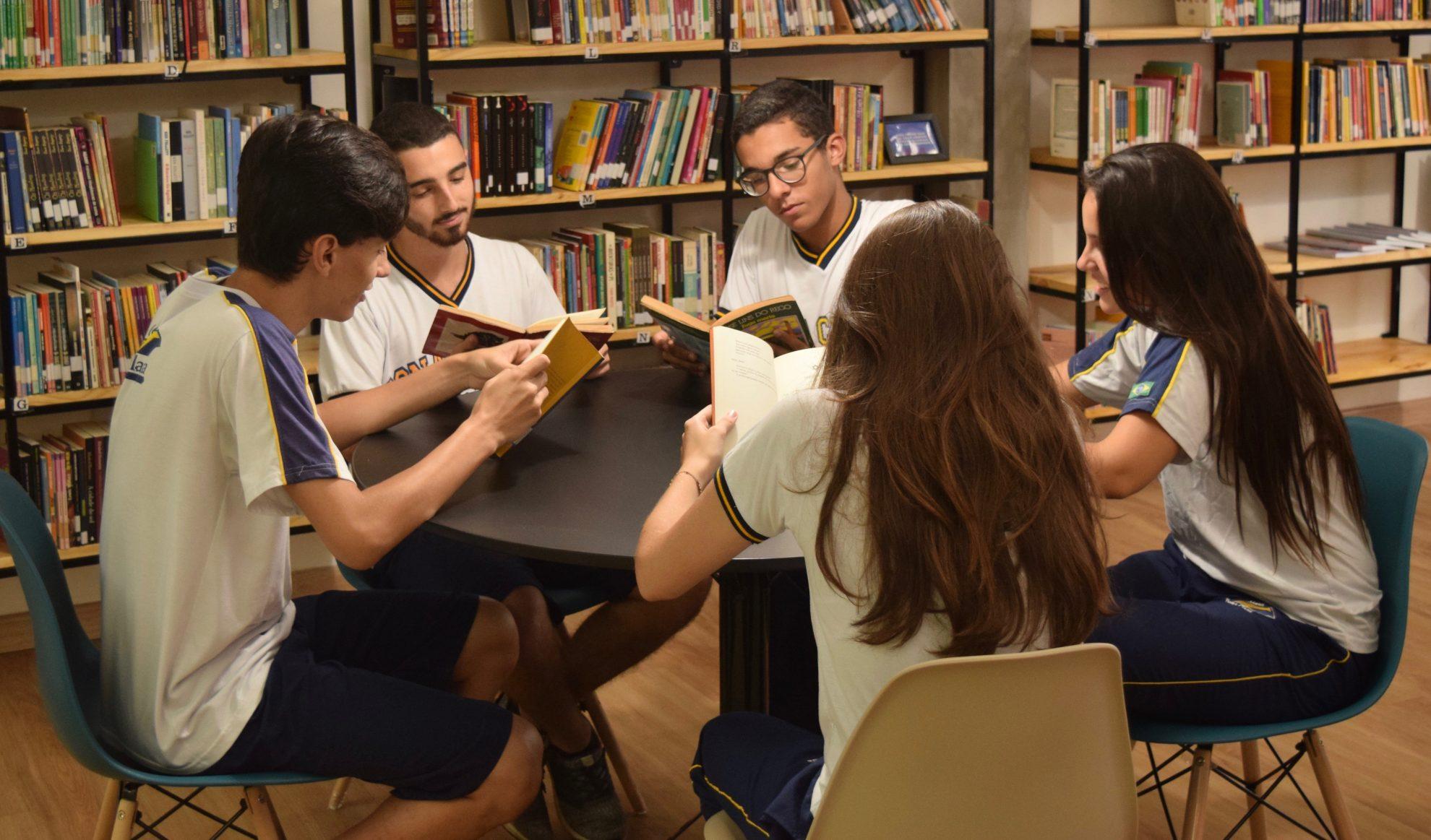 Cinco jovens sentados dentro da biblioteca criam o hábito de ler com diversas obras