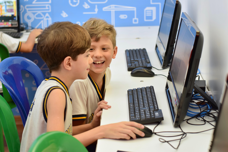 Duas crianças sentadas em frente ao computador na escola