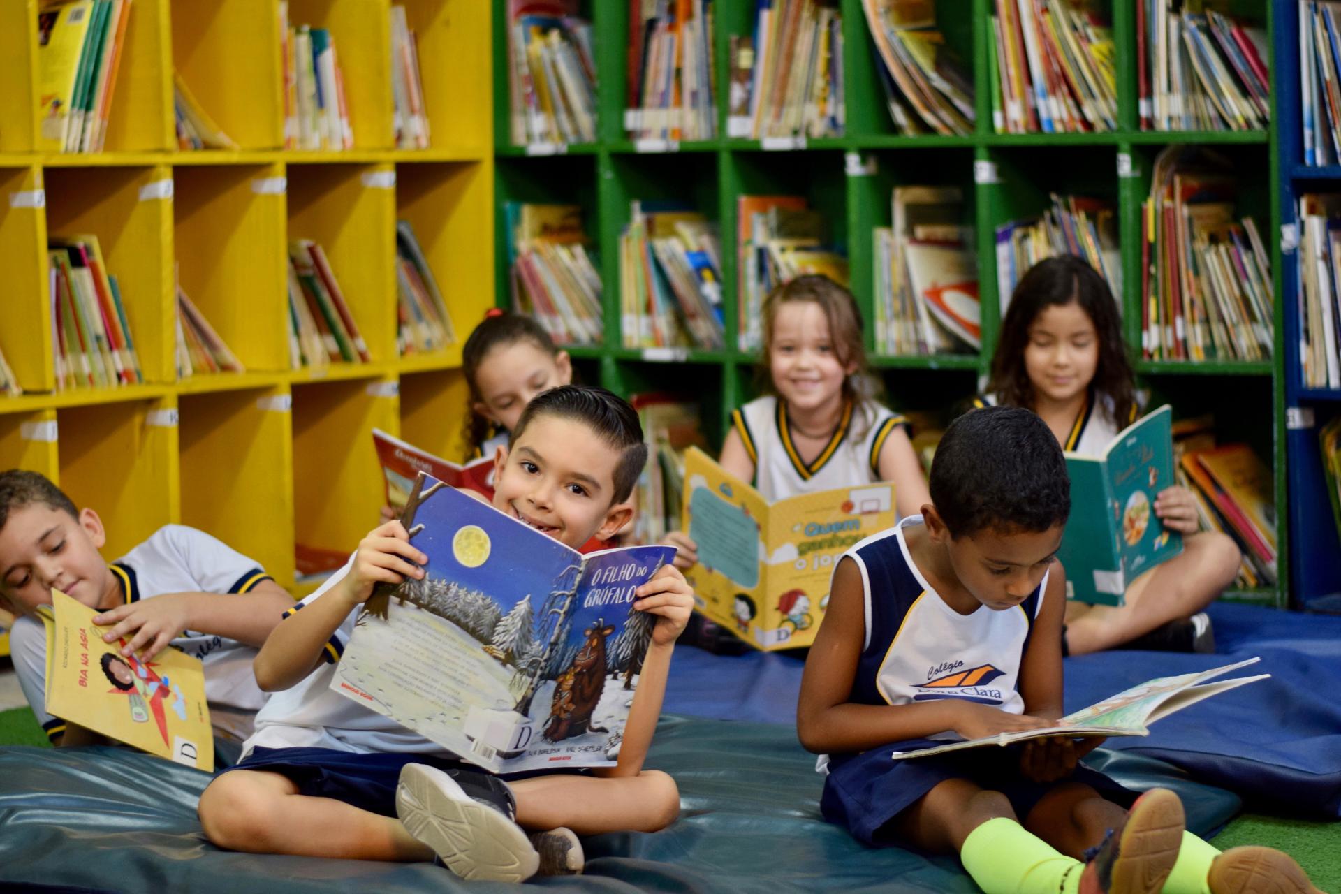 Crianças em biblioteca, lendo livros infantis em um grande puff, é o retrato da estimulação da criatividade na infância na escola