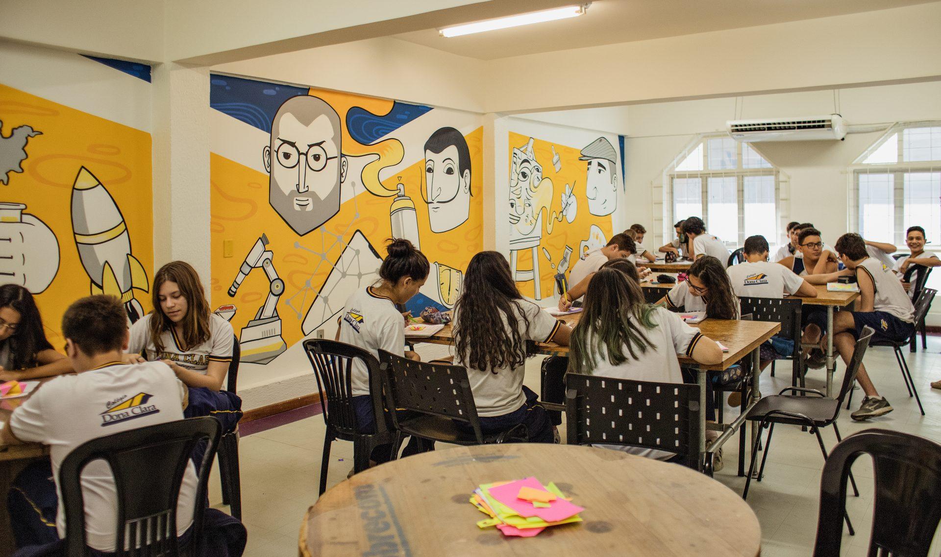 Estudantes sentados em grupos dentro da sala de aula discutem sobre as profissões do futuro